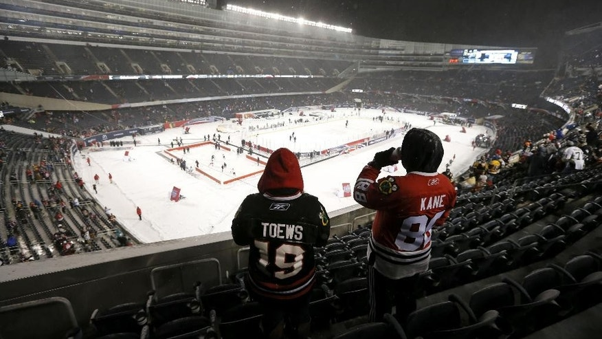 Two Chicago Blackhawks fans look out over the ice before an NHL Stadium Series hockey game between the Blackhawks and the Pittsburgh Penguins at Soldier Field on Saturday, March 1, 2014, in Chicago. (AP Photo/Charles Rex Arbogast)