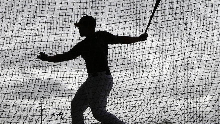 Oakland Athletics invitee catcher Bruce Maxwell hits in a batting cage as rain begins to fall before the Oakland Athletics are scheduled to play the Texas Rangers in a spring training baseball game Saturday, March 1, 2014, in Phoenix. (AP Photo/Gregory Bull)