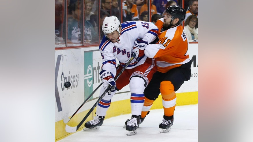 New York Rangers' Derek Dorsett, left, and Philadelphia Flyers' Andrej Meszaros battle for the puck during the third period of an NHL hockey game, Sunday, March 2, 2014, in Philadelphia. Philadelphia won 4-2. (AP Photo/Matt Slocum)