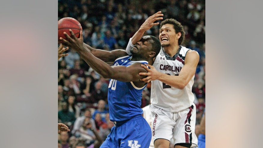 Kentucky's  Julius Randle (30) is fouled as South Carolina's Michael Carrera (24) tries to defend during the first half of an NCAA college basketball game Saturday March 1, 2014 in Columbia, S.C. (AP Photo/Mary Ann Chastain)