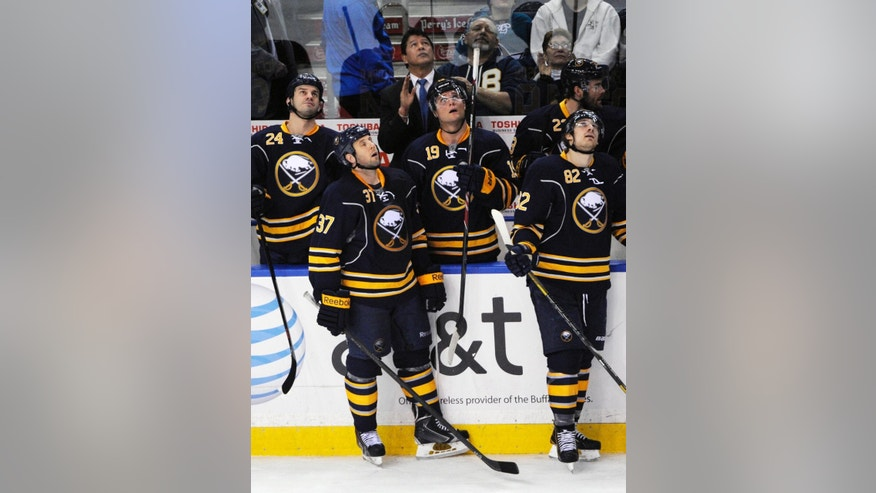Buffalo Sabres' Zenon Konopka (24), Matt Ellis (37), coach Ted Nolan, Cody Hodgson (19) and Marcus Foligno (82) look up at the replay highlights of Ryan Miller's career during the third period of an NHL hockey game against the San Jose Sharks in Buffalo, N.Y., Friday, Feb. 28, 2014. Buffalo won 4-2. Miller was traded Friday to the St. Louis Blues. (AP Photo/Gary Wiepert)