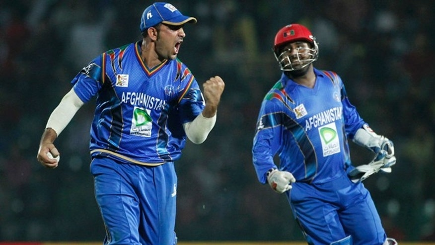 March 1, 2014: Afghanistan's Samiullah Shenwari, left, and wicketkeeper Mohammad Shahzad celebrate the dismissal of Bangladesh's Nasir Hossain during their Asia Cup 2014 one-day international cricket match in Fatullah.