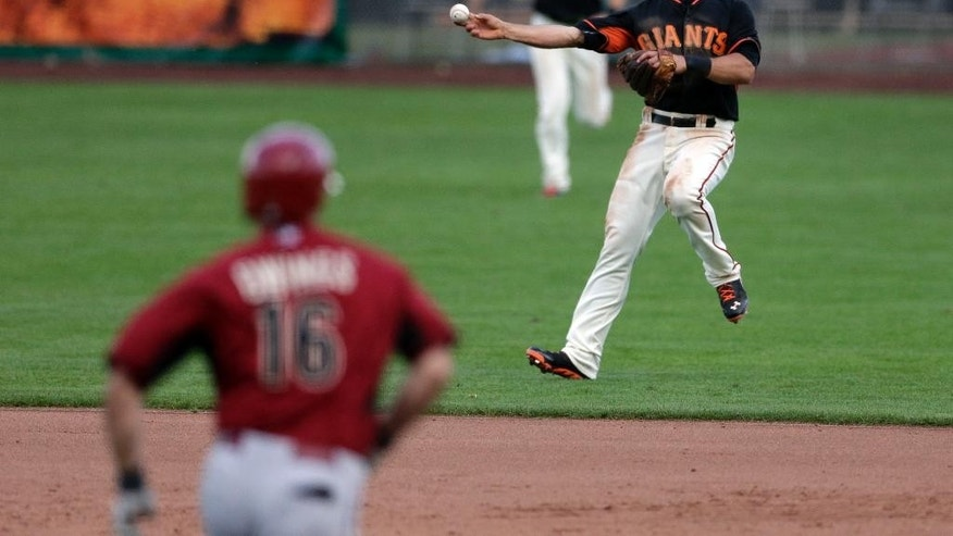 San Francisco Giants shortstop Brandon Hicks, right, makes the throw to first in time to get the out on Arizona Diamondbacks' Chris Owings, left, during the ninth inning of a spring exhibition baseball game on Sunday, March 2, 2014, in Scottsdale, Ariz. (AP Photo/Gregory Bull)
