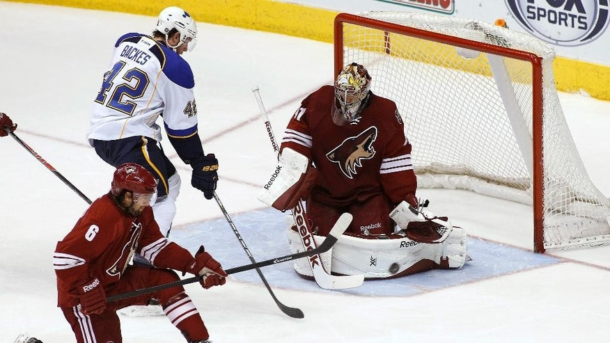 Phoenix Coyotes goaltender Mike Smith (41) makes a pad save in front of St Louis Blues' David Backes (42) as Coyotes' David Schlemko (6) looks to clear the puck during the second period of an NHL hockey game on Sunday, March 2, 2014, in Glendale, Ariz. (AP Photo/Ralph Freso)