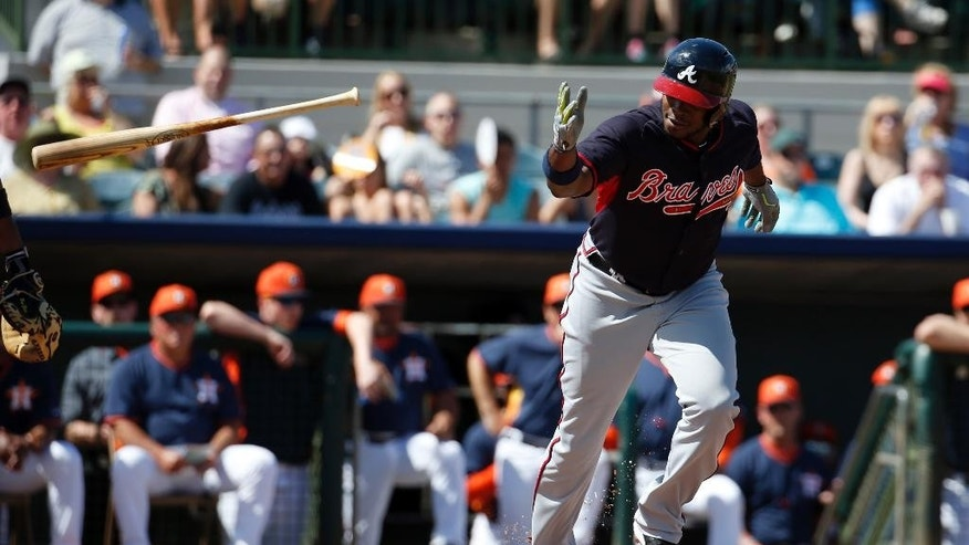 Atlanta Braves left fielder Justin Upton tosses his bat as he walks to first in the first inning of a spring exhibition baseball game against the Houston Astros, Sunday, March 2, 2014, in Kissimmee, Fla. (AP Photo/Alex Brandon)