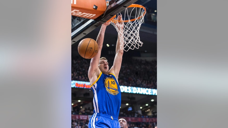 Golden State Warriors's David Lee hangs from the basket after losing possession during the first half of an NBA basketball game against the Toronto Raptors on Sunday, March 2, 2014, in Toronto. (AP Photo/The Canadian Press, Chris Young)