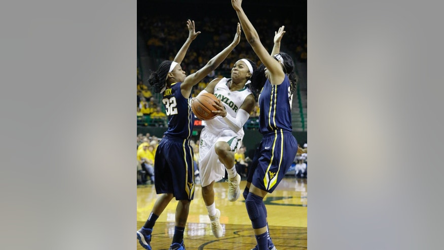 Baylor guard Odyssey Sims, center, drives between West Virginia forward Crystal Leary (32) and center Asya Bussie (20) during the first quarter of an NCAA college basketball game on Sunday, March 2, 2014, in Waco, Texas. (AP Photo/LM Otero)