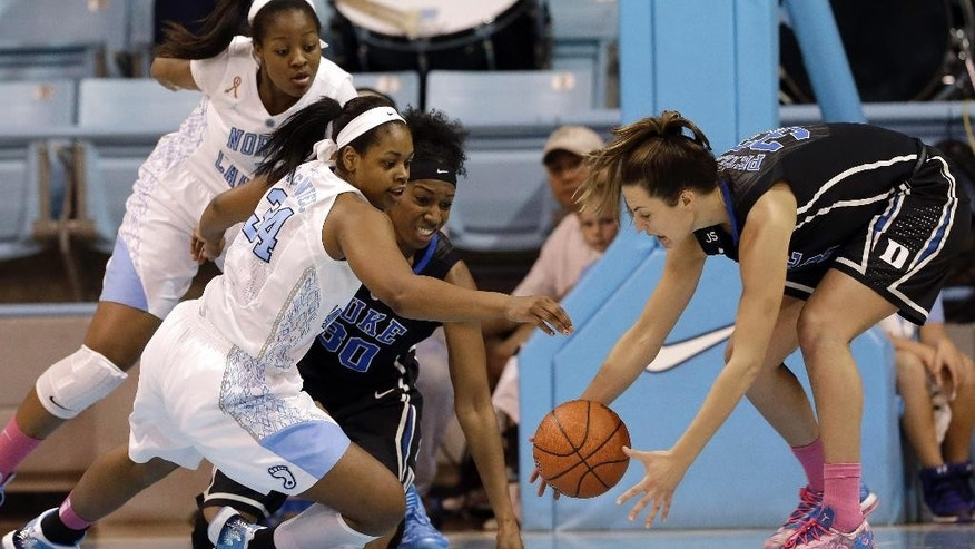 Duke's Haley Peters, right, and Amber Henson (30) reach for a loose ball against North Carolina's Xylina McDaniel (34) and Stephanie Mavunga during the first half of an NCAA college basketball game in Chapel Hill, N.C., Sunday, March 2, 2014. (AP Photo/Gerry Broome)