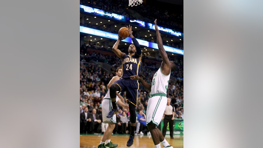 Indiana Pacers small forward Paul George (24) drives to the basket ahead of Boston Celtics power forward Brandon Bass (30) during the first half of an NBA basketball game on Saturday, March 1, 2014, in Boston. (AP Photo/Mary Schwalm)