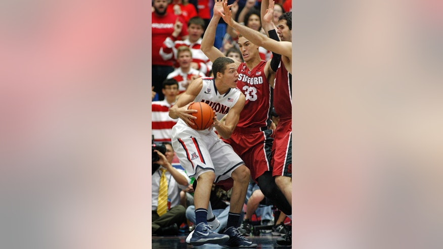 Arizona's Aaron Gordon, left, looks to pass the ball against the defense of Stanford's Dwight Powell (33 ) and Stefan Nastic, far right, in the first half of an NCAA college basketball game, Sunday, March 2, 2014 in Tucson, Ariz. (AP Photo/John MIller)