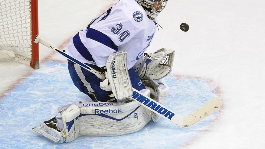 Tamp Bay Lightning goalie Ben Bishop makes a save in the first period of an NHL hockey game against the Colorado Avalanche on Sunday, March 2, 2014 in Denver. (AP Photo/Chris Schneider)