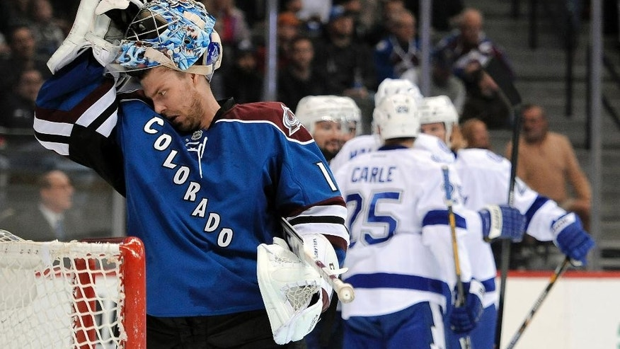 Colorado Avalanche goalie Semyon Varlamov, left, of Russia, takes off his mask as the Tampa Lightning celebrate a goal by center Nate Thompson during the second period of an NHL hockey game Sunday, March 2, 2014, in Denver.  (AP Photo/Chris Schneider)