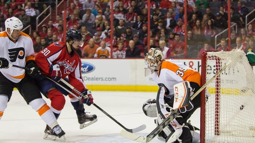 Philadelphia Flyers defenseman Nicklas Grossmann, left, tries to defend against Washington Capitals center Marcus Johansson, center, who scores a goal past Flyers goalie Steve Mason during the first period of an NHL hockey game on Sunday, March 2, 2014, in Washington. (AP Photo/ Evan Vucci)
