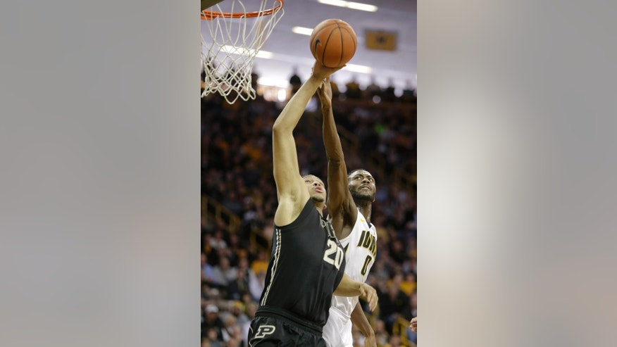Iowa center Gabriel Olaseni, right, blocks a shot by Purdue center A.J. Hammons during the first half of an NCAA college basketball game on Sunday, March 2, 2014, in Iowa City, Iowa. (AP Photo/Jim Slosiarek)