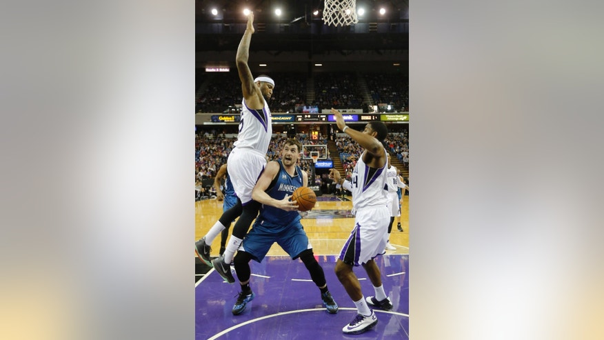 Minnesota Timberwolves forward Kevin Love, center, goes to the basket between Sacramento Kings' DeMarcus Cousins, left, and Jason Thompson during the first quarter of an NBA basketball game in Sacramento, Calif., Saturday, March 1, 2014.(AP Photo/Rich Pedroncelli)