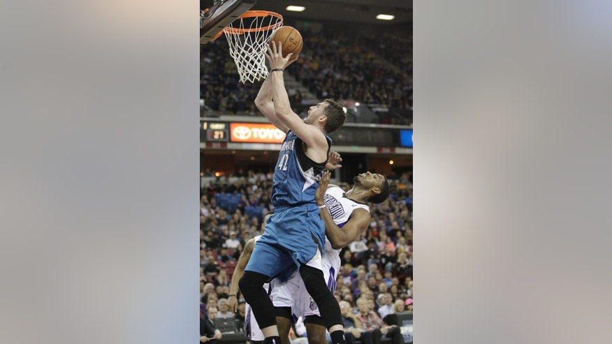 Minnesota Timberwolves forward Kevin Love, left, goes to the basket against Sacramento Kings forward Jason Thompson during the first quarter of an NBA basketball game in Sacramento, Calif., Saturday, March 1, 2014. (AP Photo/Rich Pedroncelli)
