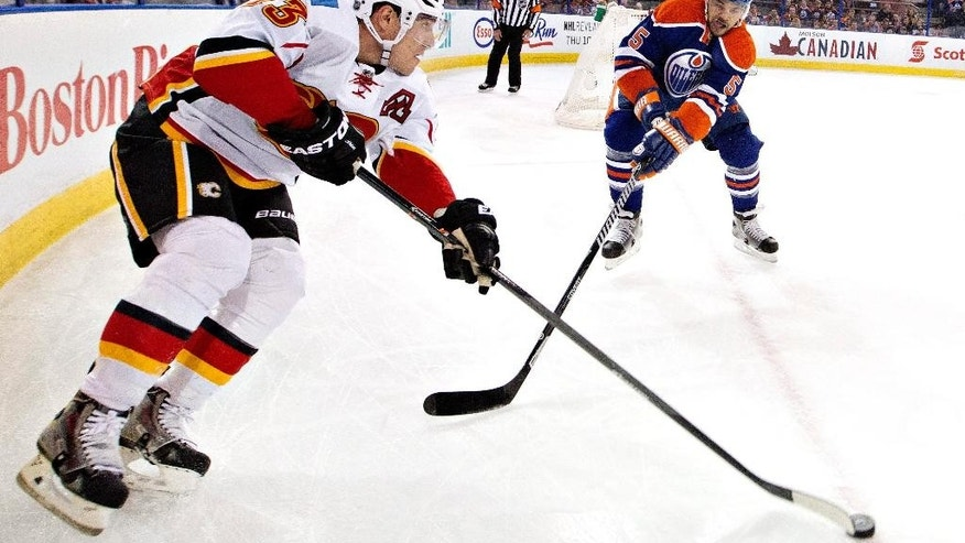 Calgary Flames' Sean Monahan (23) battles in the corner with Edmonton Oilers' Mark Fraser (5) during the first period of an NHL hockey game, Saturday, March 1, 2014 in Edmonton, Alberta. (AP Photo/The Canadian Press, Jason Franson)
