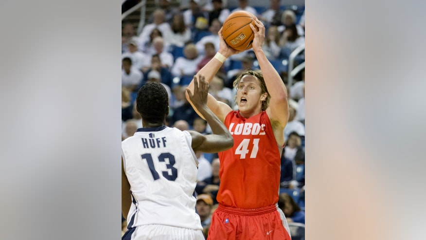 New Mexico's Cameron Bairstow looks to pass over Nevada's Cole Huff during an NCAA college basketball game Sunday, March 2, 2014, in Reno, Nev. (AP Photo/Reno Gazette-Journal, Tom R. Smedes) CARSON CITY OUT