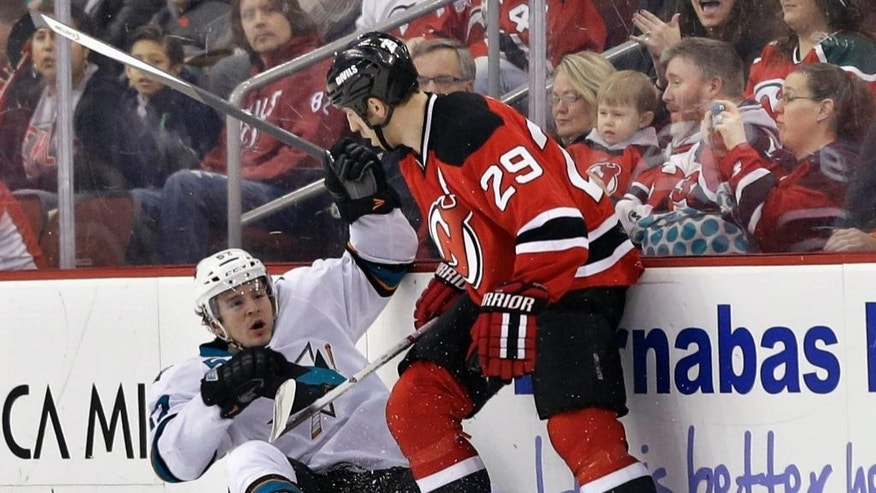 New Jersey Devils' Ryane Clowe (29) checks San Jose Sharks' Tommy Wingels (57) during the first period of an NHL hockey game Sunday, March. 2, 2014, in Newark, N.J. (AP Photo/Mel Evans)