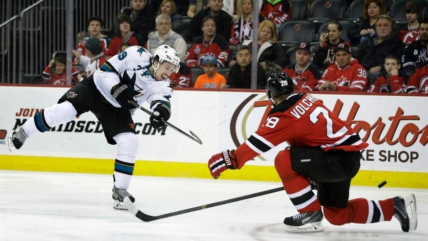San Jose Sharks' Logan Couture (39) takes a shot past New Jersey Devils' Anton Volchenkov (28), of Russia, during the first period of an NHL hockey game Sunday, March. 2, 2014, in Newark, N.J. (AP Photo/Mel Evans)