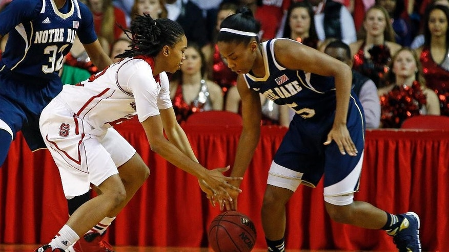 Notre Dame's Lindsay Allen, right, attempts to steal the ball from North Carolina State's Krystal Barrett during the first half of an NCAA college basketball game in Raleigh, N.C., Sunday, March 2, 2014. (AP Photo/Karl B DeBlaker)