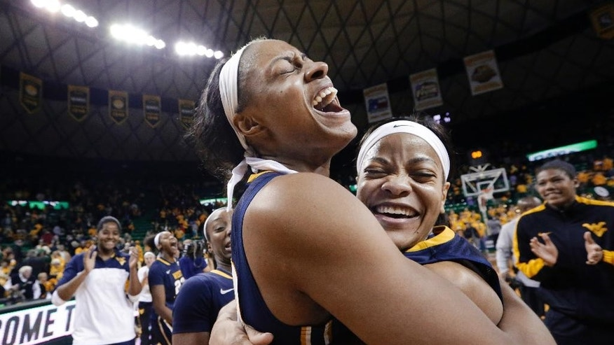 West Virginia center Asya Bussie, left, hugs teammate Christal Caldwell after an NCAA college basketball game against Baylor on Sunday, March 2, 2014, in Waco, Texas. West Virginia won 71-69. (AP Photo/LM Otero)