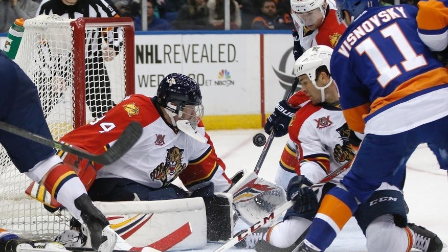 Florida Panthers goalie Tim Thomas (34), Panthers right wing Scottie Upshall (19) and a teammate defend with New York Islanders defenseman Lubomir Visnovsky (11), of Slovakia, close by in the second period of an NHL hockey game in Uniondale, N.Y., Sunday, March 2, 2014. (AP Photo/Kathy Willens)