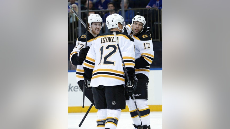 Boston Bruins' Dougie Hamilton, left, and Milan Lucic, right, celebrate Jarome Iginla's goal during the first period of an NHL hockey game against the New York Rangers on Sunday, March 2, 2014, in New York. (AP Photo/Seth Wenig)