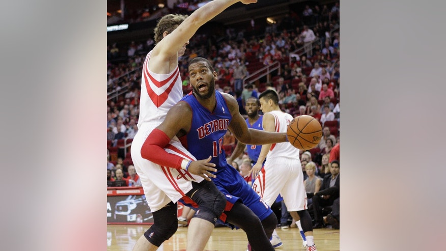 Detroit Pistons forward Greg Monroe (10) drives to the basket around Houston Rockets' Omer Asik during the first half of an NBA basketball game, Saturday, March 1, 2014, in Houston. (AP Photo/Bob Levey)
