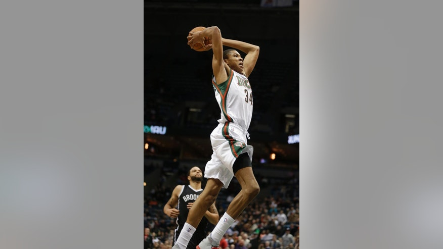 Milwaukee Bucks' Giannis Antetokounmpo, right, dunks against Brooklyn Nets' Deron Williams, left, in the second half of an NBA basketball game Saturday, March 1, 2014, in Milwaukee. (AP Photo/Jeffrey Phelps)