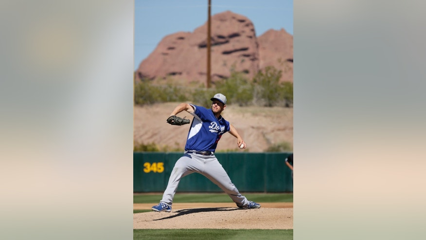 Los Angeles Dodgers pitcher Clayton Kershaw throws a warm up pitch before pitching against the Oakland Athletics during the third inning of a spring training baseball game Monday, March 3, 2014, in Phoenix. (AP Photo/Gregory Bull)