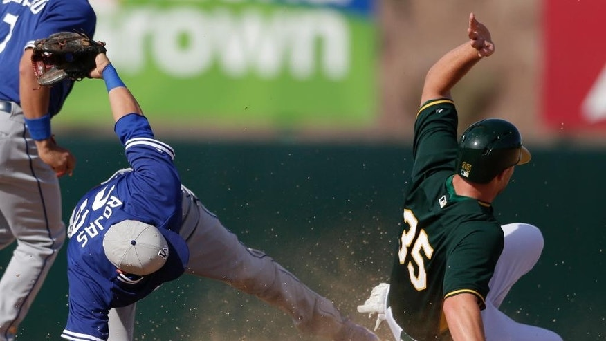 Los Angeles Dodgers shortstop Miguel Rojas, left, reaches with his foot towards second base as Oakland Athletics' Chris Gimenez, right, is caught stealing second  during the seventh inning of a spring training baseball game Monday, March 3, 2014, in Phoenix. (AP Photo/Gregory Bull)