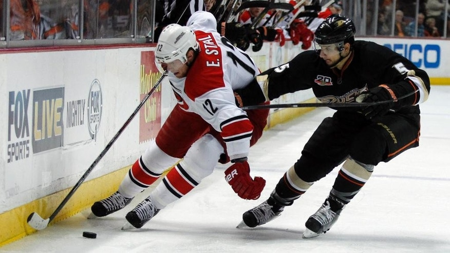 Carolina Hurricanes center Eric Staal (12) controls the puck against Anaheim Ducks defenseman Luca Sbisa (5), of Italy, during the first period of an NHL hockey game Sunday, March 2, 2014, in Anaheim, Calif. (AP Photo/Alex Gallardo)