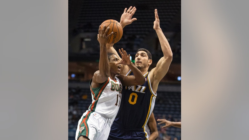 Milwaukee Bucks' Brandon Knight, left, drives on Utah Jazz Enes Kanter during the first half of an NBA basketball game Monday, March 3, 2014, in Milwaukee. (AP Photo/Tom Lynn)