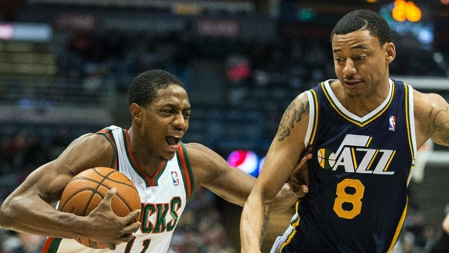 Milwaukee Bucks' Brandon Knight, left, is fouled by Utah Jazz Diante Garrett during the first half of an NBA basketball game Monday, March 3, 2014, in Milwaukee. (AP Photo/Tom Lynn)