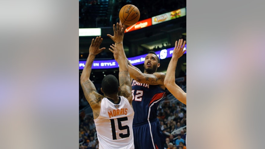Atlanta Hawks' Mike Scott (32) shoots over Phoenix Suns' Marcus Morris during the first half of an NBA basketball game, Sunday, March 2, 2014, in Phoenix.(AP Photo/Matt York)