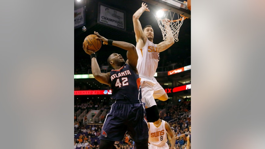 Atlanta Hawks' Elton Brand (42) shoots over Phoenix Suns' Miles Plumlee during the first half of an NBA basketball game, Sunday, March 2, 2014, in Phoenix. (AP Photo/Matt York)