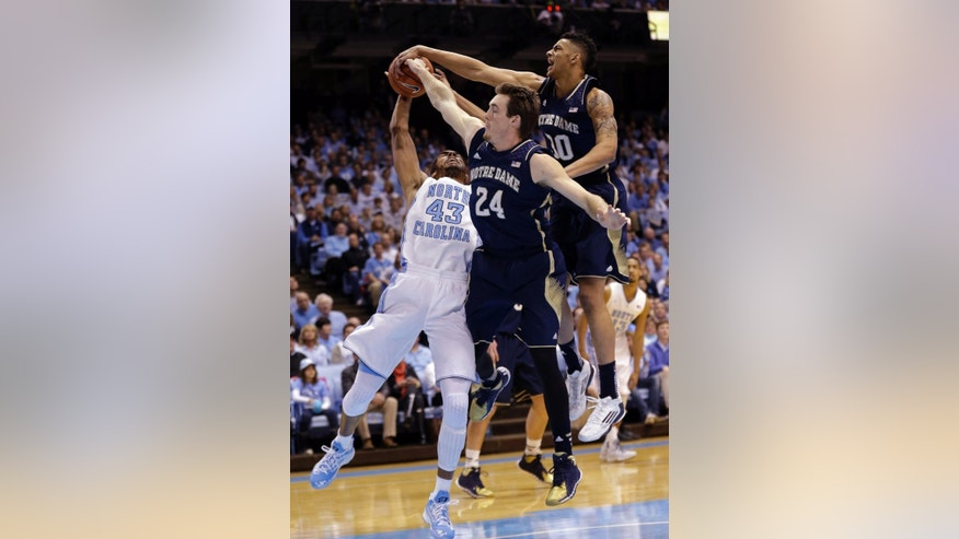 North Carolina's James Michael McAdoo (43) is blocked by Notre Dame's Pat Connaughton (24) and Zach Auguste during the first half of an NCAA college basketball game in Chapel Hill, N.C., Monday, March 3, 2014. (AP Photo/Gerry Broome)