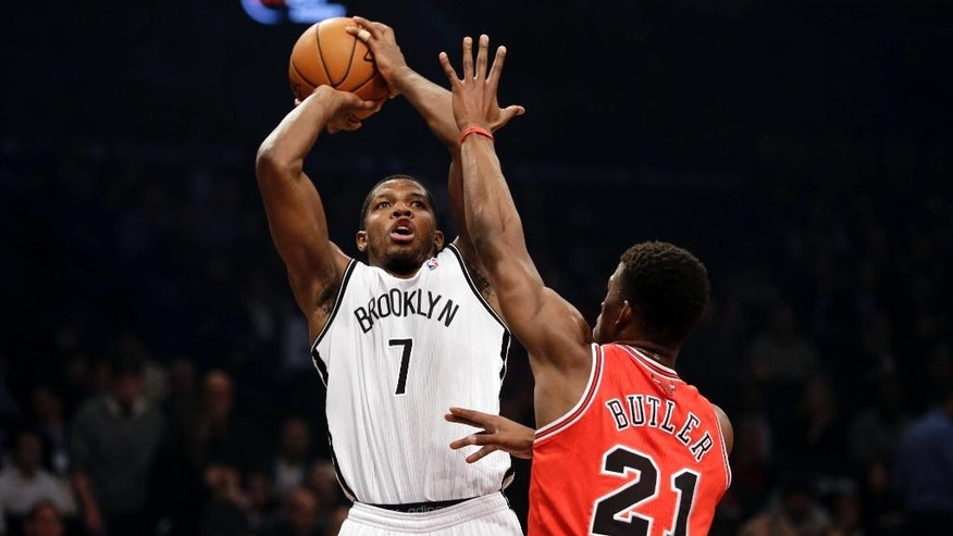 Brooklyn Nets' Joe Johnson, left, shoots over Chicago Bulls' Jimmy Butler during the first half of an NBA basketball game Monday, March 3, 2014, in New York. (AP Photo/Seth Wenig)