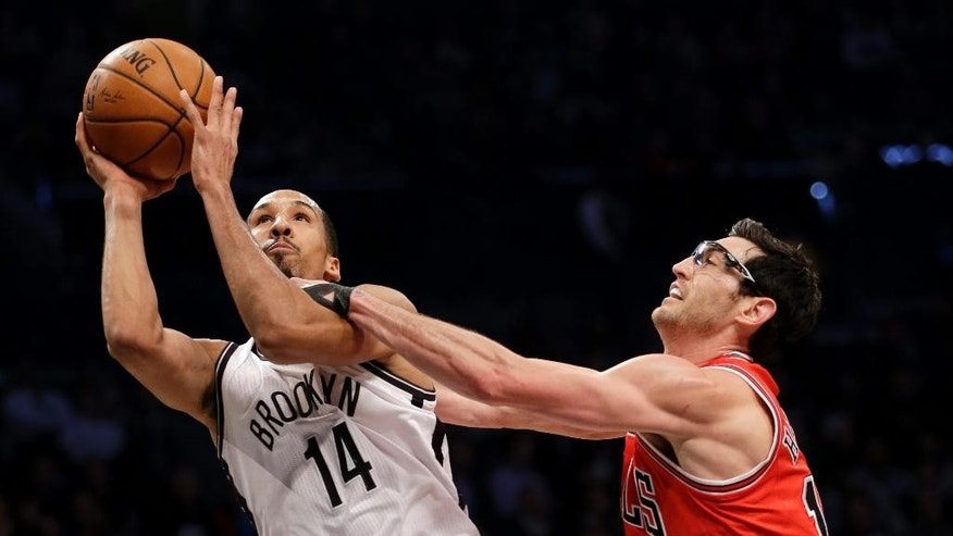 Chicago Bulls' Kirk Hinrich, right, fouls Brooklyn Nets' Shaun Livingston as he drives to the basket during the first half of an NBA basketball game Monday, March 3, 2014, in New York. (AP Photo/Seth Wenig)