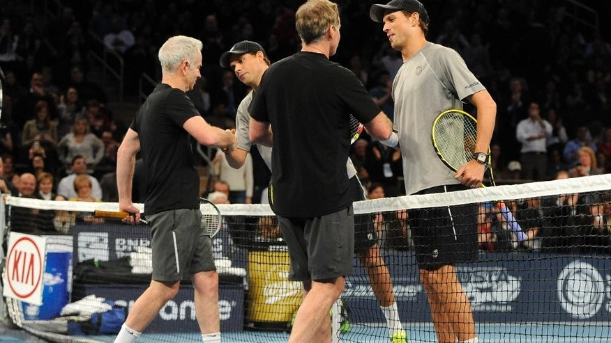 John, left, and Patrick McEnroe shake hands with Bob, second from left, and Mike Bryan after the Bryans won 8-3 in the BNP Paribas Showdown Tennis Tournament on Monday, March 3, 2014, in New York. (AP Photo/Kathy Kmonicek)