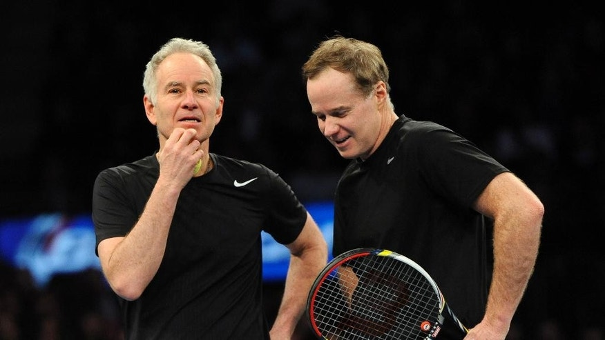 John, left, and Patrick McEnroe confer during their match against Mike and Bob Bryan in the BNP Paribas Showdown Tennis Tournament on Monday, March 3, 2014, in New York. The Bryans won 8-3. (AP Photo/Kathy Kmonicek)