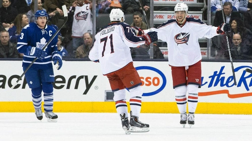 Toronto Maple Leafs Dion Phaneuf, left, stands near as Columbus Blue Jackets Artem Anismov, right, celebrates with Nick Folingo after Anismov scored a goal during the second period of an NHL hockey game in Toronto on Monday, March 3, 2014. (AP Photo/The Canadian Press, Chris Young)