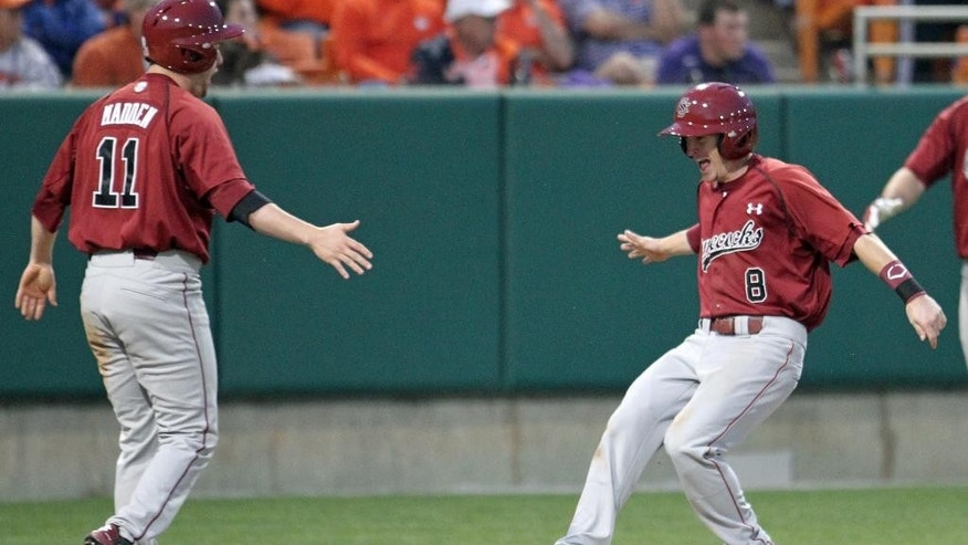 South Carolina's Marcus Mooney, right, celebrates with Zack Madden after they scored the winning runs in the ninth inning to defeat Clemson 5-3 in an NCAA college baseball game on Sunday, March 2, 2014, in Clemson, S.C. (AP Photo/Anderson Independent-Mail, Mark Crammer) GREENVILLE NEWS OUT; SENECA JOURNAL OUT