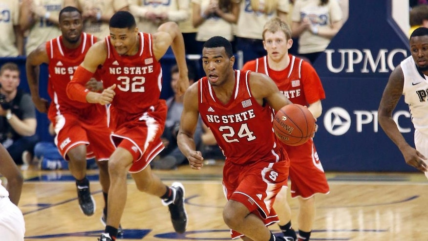 North Carolina State's T.J. Warren (24) leads the pack of teammates Kyle Washington (32), Tyler Lewis, right, and Desmond Lee, left, after making a steal against Pittsburgh during the second half of an NCAA college basketball game on Monday, March 3, 2014, in Pittsburgh. (AP Photo/Keith Srakocic)
