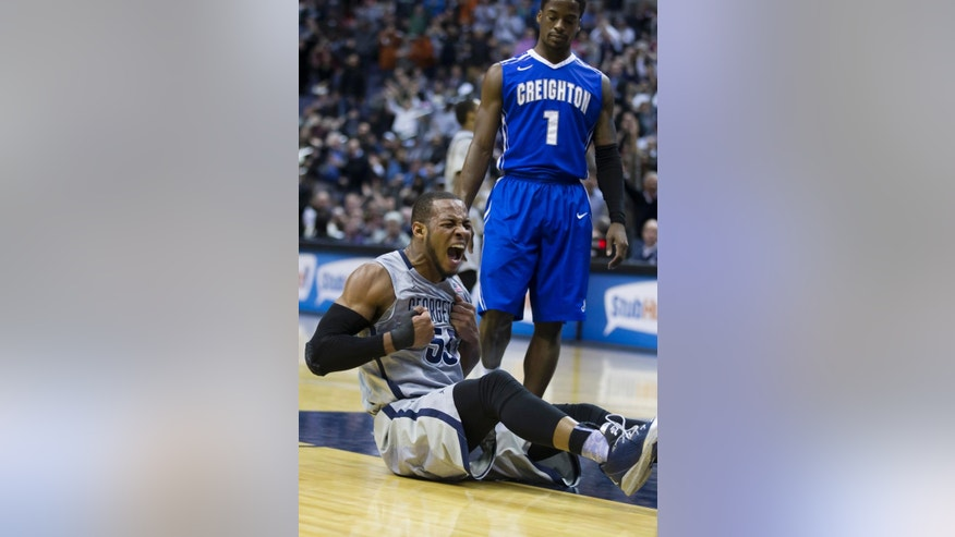 Creighton guard Austin Chatman, right, watches as Georgetown guard Jabril Trawick beats his chest and celebrates his dunk during the first half of an NCAA basketball game on Tuesday, March 4, 2014, in Washington. (AP Photo/ Evan Vucci)