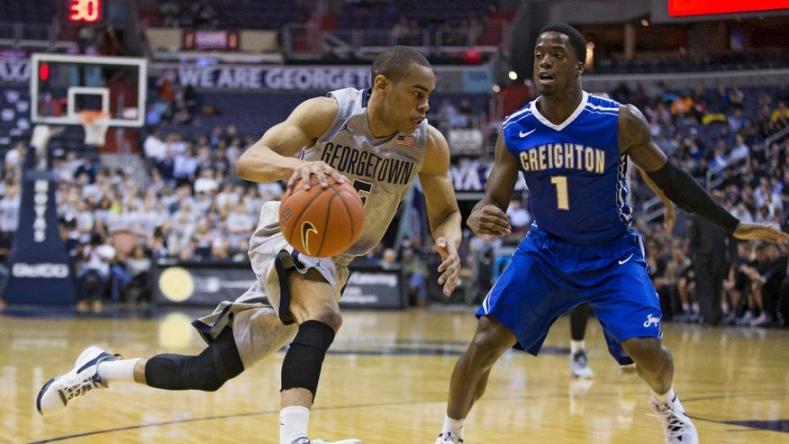 Georgetown guard Markel Starks (5) drives past Creighton guard Austin Chatman (1) during the first half of an NCAA basketball game on Tuesday, March 4, 2014, in Washington. (AP Photo/ Evan Vucci)