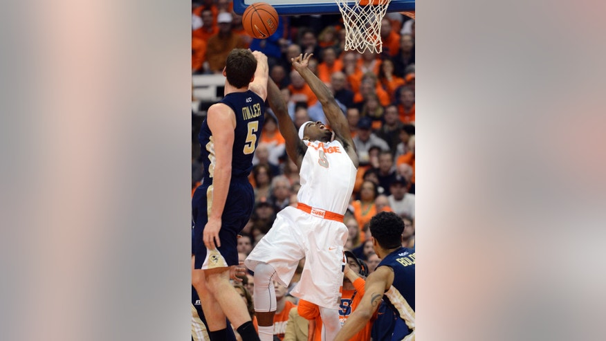 Syracuse's C. J. Fair has his shot blocked by Georgia Tech's Daniel Miller during the first half of an NCAA college basketball game in Syracuse, N.Y., Tuesday, March 4, 2014. (AP Photo/Kevin Rivoli)