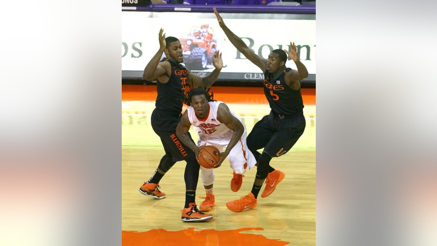 Clemson's Rod Hall, center, passes under pressure of Miami's James Kelly, left, and Davon Reed, right, during the second half of the NCAA Men's basketball game at Littlejohn Coliseum Tuesday, March 4, 2014, in Clemson, S.C..   Clemson won 58-54, improving to 19-10. (AP Photo/The Independent-Mail, Ken Ruinard) THE GREENVILLE NEWS OUT, SENECA NEWS OUT