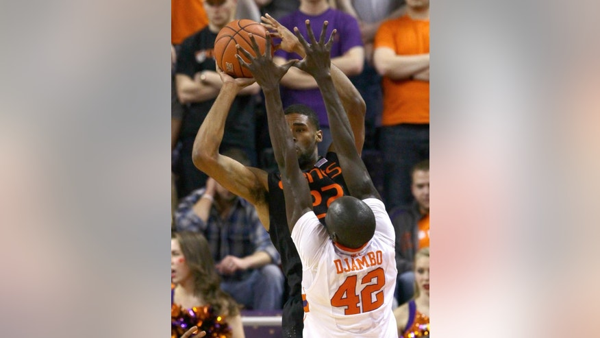 Miami's Donnavan Kirk, rear, passes to a teammate near Clemson's Ibrahim Djambo during the first half of  an NCAA college basketball game at Littlejohn Coliseum Tuesday, March 4, 2014, in Clemson, S.C.. (AP PHOTO/Anderson Independent Mail, Ken Ruinard)  THE GREENVILLE NEWS OUT, SENECA NEWS OUT